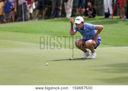 KUALA LUMPUR, MALAYSIA - OCTOBER 29, 2016: Candie Kung of Chinese Taipei checks the line of the green at the TPC Golf Course at the 2016 Sime Darby LPGA Malaysia golf tournament.
