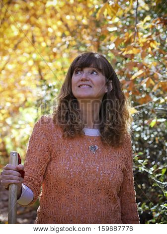 A Portrait of a Woman Hiking with a Walking Stick in the Fall