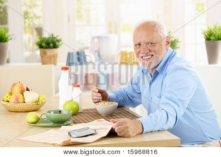 Cheerful healthy senior man having cereal for breakfast in kitchen, smiling at camera.?