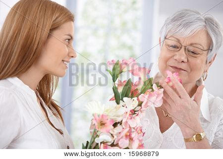 Pretty woman greeting her mother at mother's day, giving flowers, both smiling.?