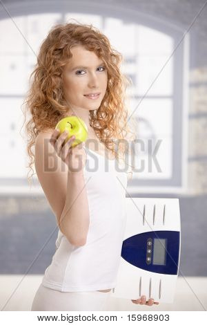 Pretty female holding apple and scale in hands, dieting.?