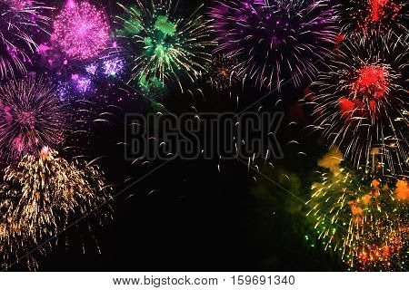 Greeting card with various colorful fireworks on black background. Multicolored Web banner. Can be used to design of holidays: Christmas New year anniversary independence day Birthday