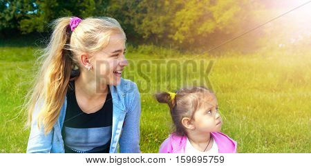 Two girls sit on a green lawn and laughs in the morning