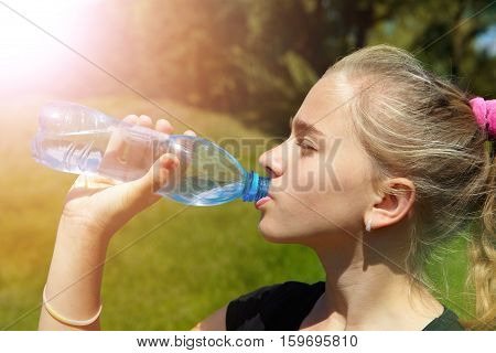 Young girl on a green lawn and drinks water in the morning