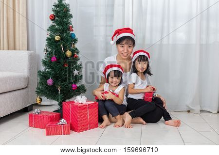 Asian Chinese Mother And Daughters Sitting Next To Christmas Tree