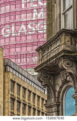 The corner facade of an old sandstone building and the retro style college of building and printing in the background sandwiches a modern building in a scene from the Scottish city of Glasgow.