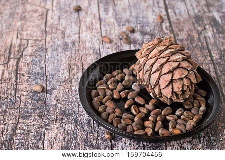 Cedar cones with nuts on black ceramic plate on an old wooden table.
