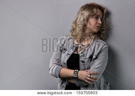 Sad blond woman with arms crossed on white background