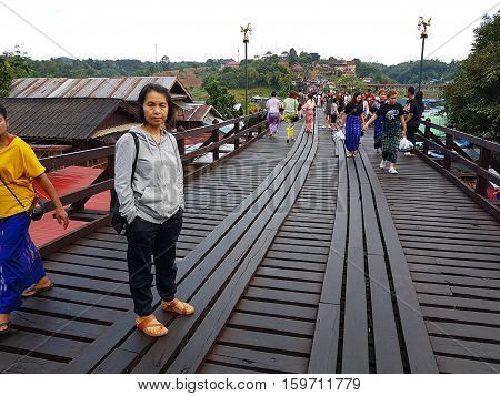 KANCHANABURI THAILAND - NOVEMBER 25: unidentified woman taking a photo at the old wooden Mon Bridge in Sangkhla Buri with crowd in the morning on November 25 2016 in Kanchanaburi Thailand