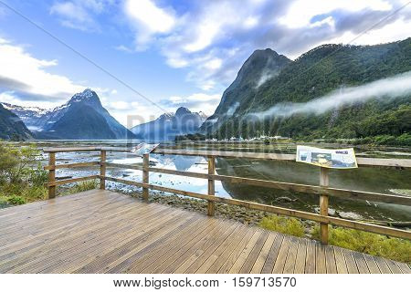 MILFORD SOUND, NEW ZEALAND - OCTOBER 27, 2016: Wooden platform facing to lake with mountain reflection at Milford Sound Fiordland, New Zealand
