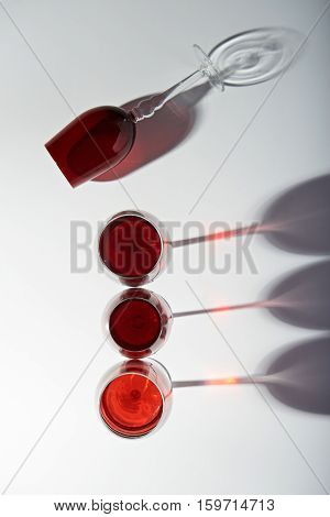 Line of red wine glasses isolated on white background