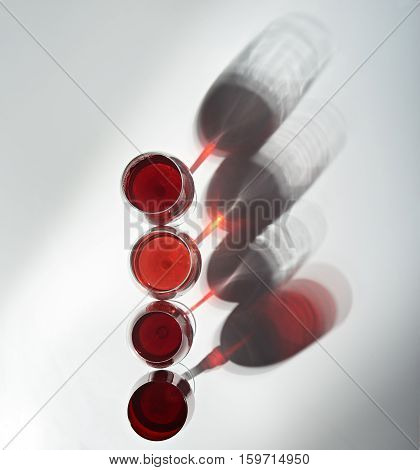 four wine glasses with red wine stand on white table