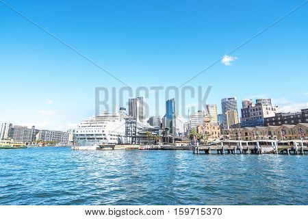SYDNEY AUSTRALIA - AUGUST 26 2016: Cruise ship in front of Opera House in Sydney harbour. Ferries are used by commuters as a pleasant way to get into the city.