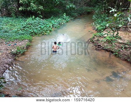 KANCHANABURI THAILAND - NOVEMBER 26: unidentified asian people swimming in the Sai Yok Yai waterfalls on November 26 2016 in Kanchanaburi Thailand