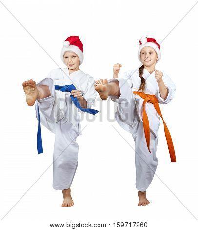 Girl and boy in Santa Claus caps beat kick leg forward