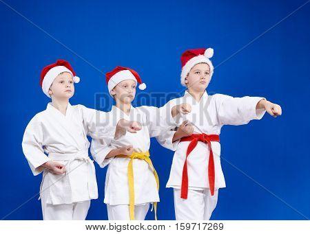 In caps of Santa Claus three athletes beat punch arm