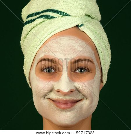 Portrait of woman with face mask and towel on dark green background.