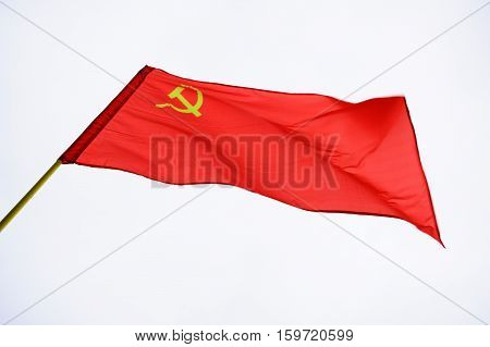 Red Soviet flag on bright sky in windy weather