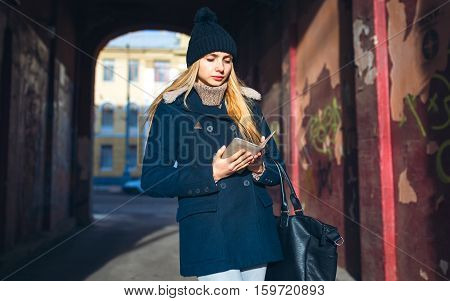 Girl in a blue coat in the city arch