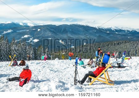 people relax sitting on the snow in winter resort