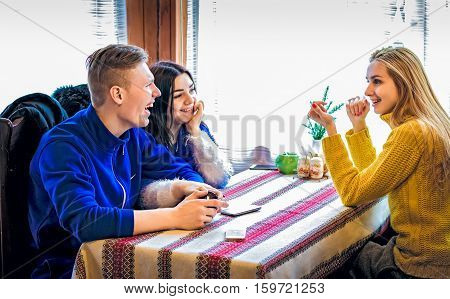 friends in winter clothes sitting at the table talking and laughing