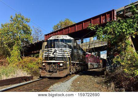Jersey City, New Jersey - November 13, 2016: Freight train passing under bridge in Jersey City New Jersey.