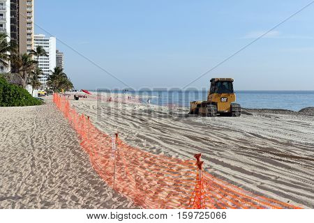 Fort Lauderdale FL USA - March 3 2016: Fenced in beach with a bulldozer replenishing sand in a nourishment project. An earth mover spreads beach restoration sand