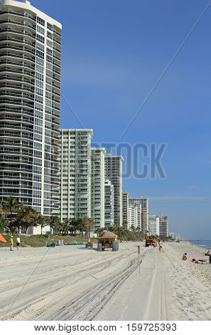 Fort Lauderdale FL USA - March 3 2016: Dump trucks with sand leave beach tracks in beach restoration. Dump trucks with sand pass people to replenish the beach.