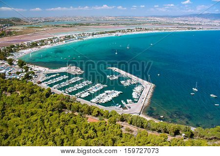 Areal view on Cagliari with green forest a port with boats famous beach Il Poetto and mountains in Sardinia Italy.