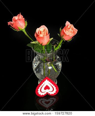 Roses and heart from fabric. Three pink roses in a vase from transparent glass on a black background with reflection. About a vase decorative heart from red fabric - a love symbol lies
