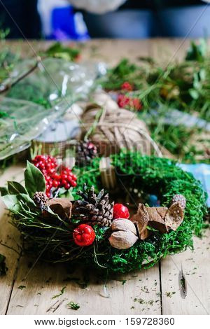 women make traditional christmas door wreath with moss and berry