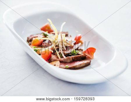 sliced beef with vegetable garnish