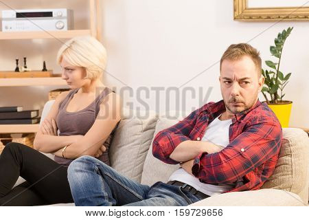 Closeup picture of offended couple man and woman sitting on sofa with their arms crossed or folded at home. Angry, disappointed, sad, having quarrel.