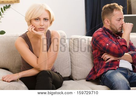 Offended couple man and woman do not speak to each other while sitting on sofa at home. Disappointed and sad blond lady looking at camera.