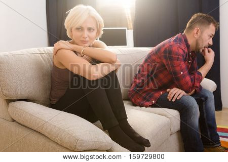 Offended couple man and woman looking sad and disappointed after quarrel concerning family life. Couple in love sitting on sofa or couch at home.