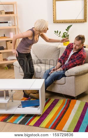Couple man and woman having conflict about family life at home. Blond lady screaming and shouting at her husband while he is sitting on sifa or couch.