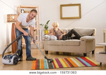 Handsome man using vacuum cleaner for cleaning floor while his wife resting on sofa or couch at home. Family concept. Clean atmosphere at home.