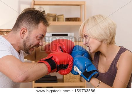 Angry couple man and woman having battle at home. Man and woman screaming, shouting with red and blue boxing gloves on fighting.