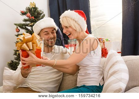 Happy blond lady receiving beautiful present or gift from her husband. Couple man and woman celebrating New Year or Christmas. New Year or Christmas concept.