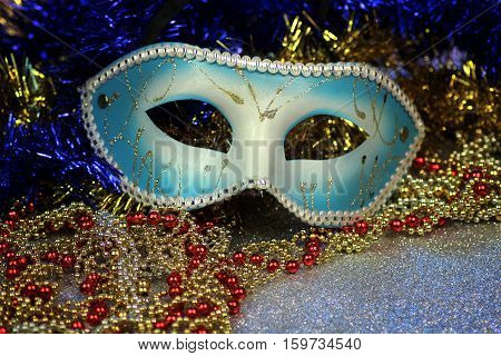 Brilliant blue carnival mask close up on shiny background with festive colored garlands.
