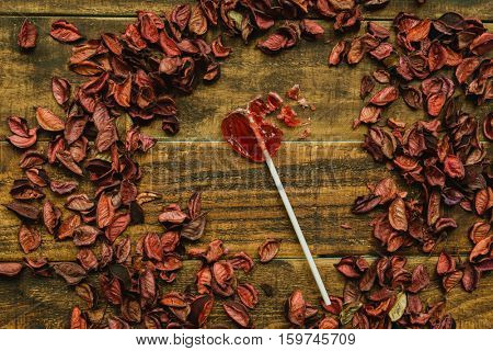 Broken red lollipo with heart shape on a wooden background
