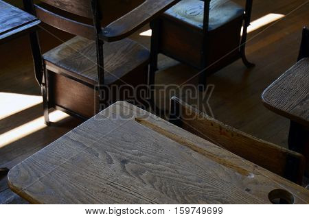 An abstract image of vintage wooden school desks in a one room school house.