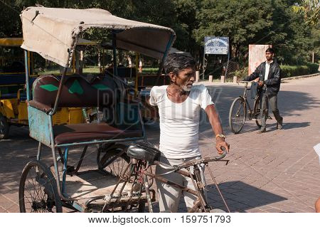 AGRA INDIA - Nov 27 2016: Unidentified men drives pedicab in front of Western Gage of Taj Mahal the monument of love on 27 November 2016.