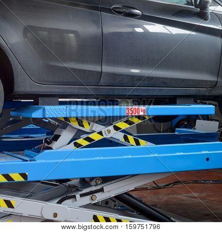 A car ready for fix on a workshop bridge