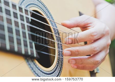 close up image of playing acoustic guitar