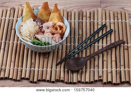Thai noodle with pink tofu soup topped rugby fishball ,wonton, porkball ,boiled porkblood ,pork rind ,coriander and white mushroom call Yen Ta Fo in Thai