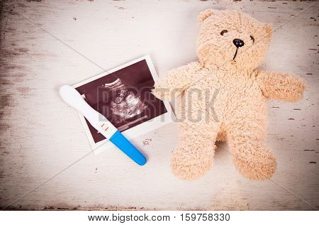 ultrasound with pregnancy test and baby teddy bear on wooden background