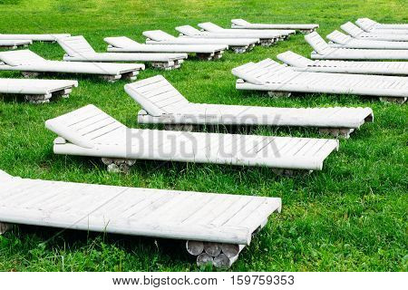 White wooden sunbeds on the green grass