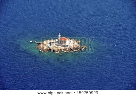 Lighthouse On Small Rock Surrounded With Sea From Above