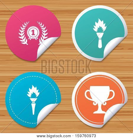 Round stickers or website banners. First place award cup icons. Laurel wreath sign. Torch fire flame symbol. Prize for winner. Circle badges with bended corner. Vector